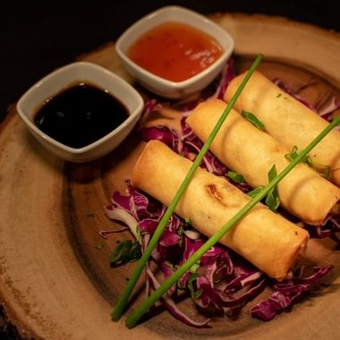 a selection of Chinese style spring rolls accompanied by a selection of sauces from above