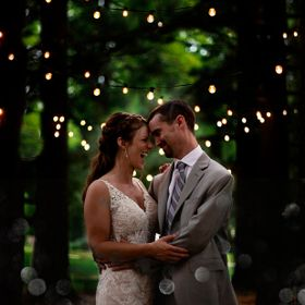 This is a portrait of a Bride and Groom standing where they walked down the aisle. It was a beautiful night as it began to get dark, and the hang...