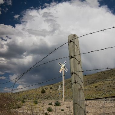 Grasshopper Creek, MT, railroad crossing and barbed wire fencing.