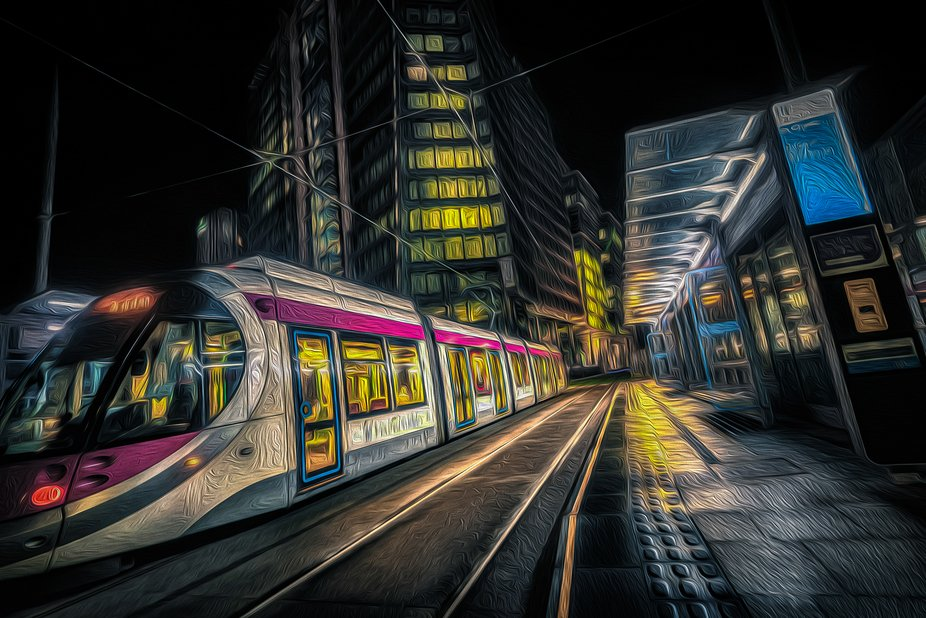 The trams of Birmingham, UK shot at night as the tram stops at the St Chads tram stop with Three ...