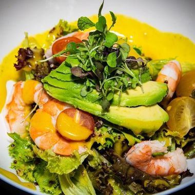 a close up shot taken of a prawn and avocado mixed leaf salad with a lemon and herb dressing