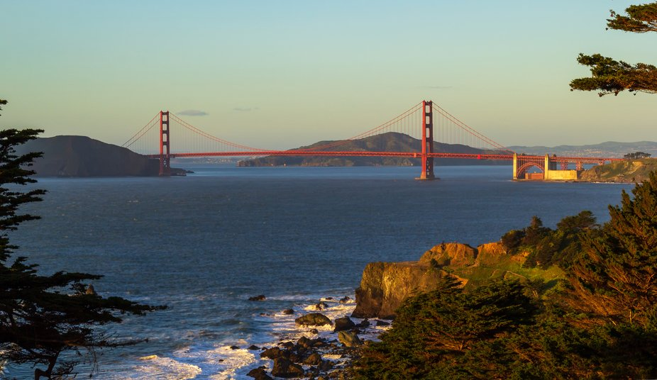 The sun shines on the Golden Gate and rocks below as it sets.