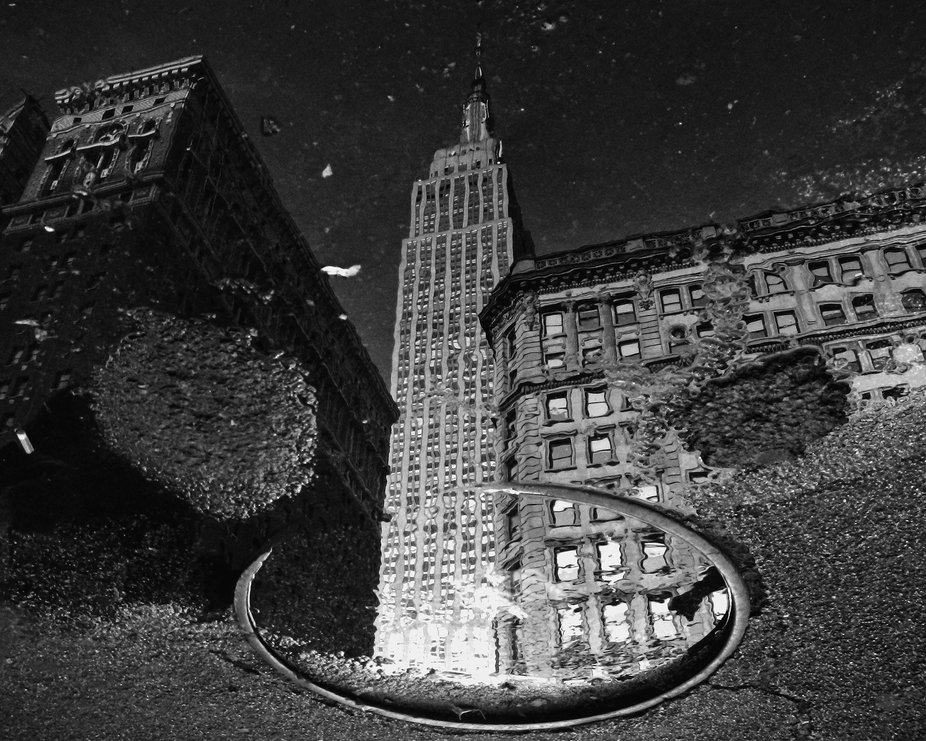 Reflection of Empire State building from street after rain