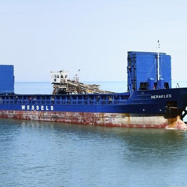 A cargo vessel named Herakles being loaded with stone at a quarry Jetty