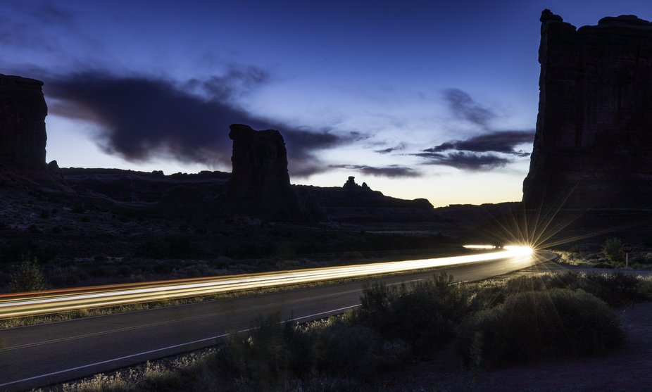 A long exposure of cars leaving Arches National Park just after sunset.