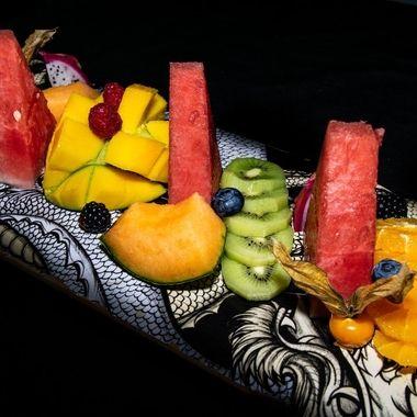 an amazing tropical fruit platter presented on a skateboard deck