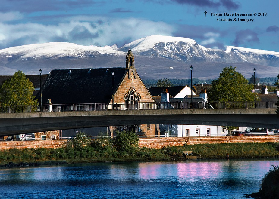 Inverness Methodist Church on the river Ness with the Scotish Highlands in the background