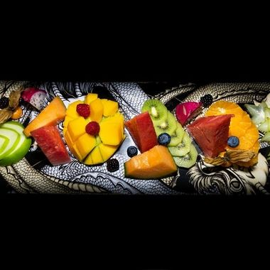 an amazing fresh and tasty tropical fruit platter presented on a skateboard deck birds eye view