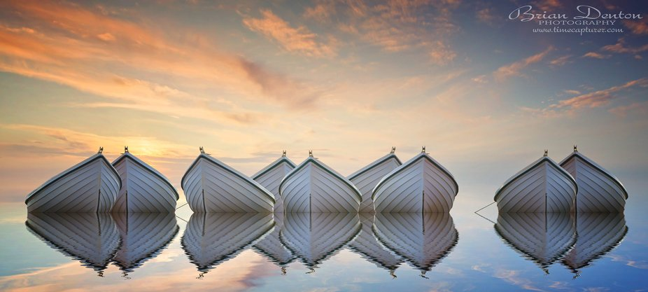 Nine white boats at sunset.