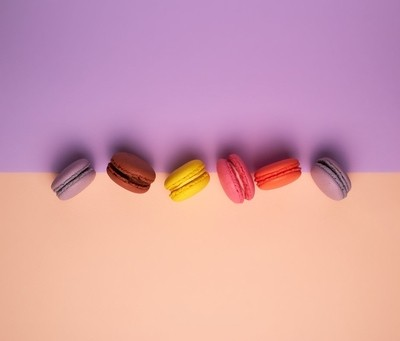 six multi-colored macarons with cream on a purple-beige background