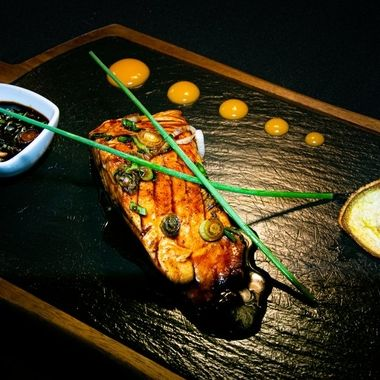 a fillet of Canadian salmon cooked in a teriyaki sauce served with extra sticky sauce and grilled vegetables