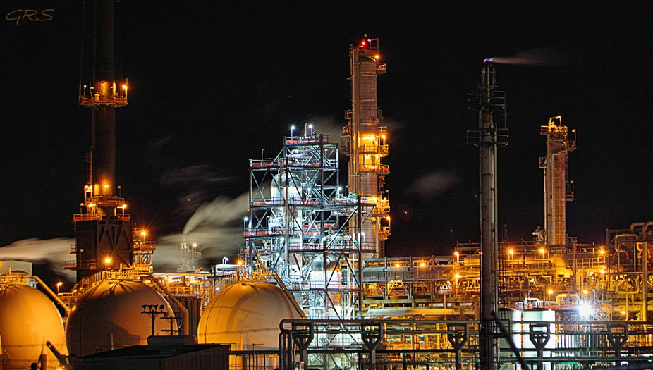 Oil refinery at night appears like an eerie city full of lights but no people.