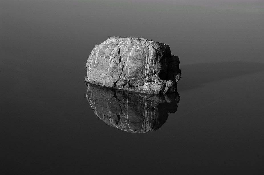 A stone erect in the middle of nowhere in a lake, how come, I don't know? but at sunrise...