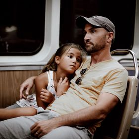 After a long day in Chicago for the first time, young girl, still young enough to find comfort in her dad.