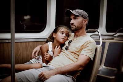 Dad and daughter on city transportation after a long day