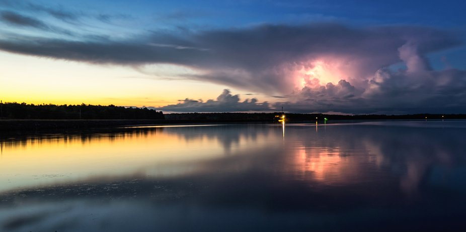 Lightning was seen illuminating an anvil cloud as a storm passed along the distant shore of this ...