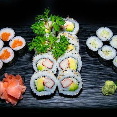 a selection of salmon and avocado hosomaki and california sushi rolls
