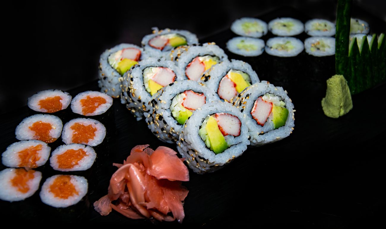 a close up shot of a selection of Hosomaki and California sushi rolls served with ginger and wasabi
