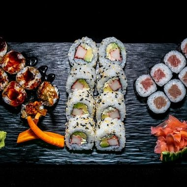a selection of different types of sushi rolls  presented on a black ceramic plate garnished with ginger and wasabi