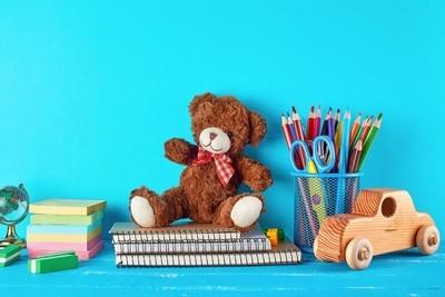 school supplies: notebook, pencils, stickers, scissors on a blue background
