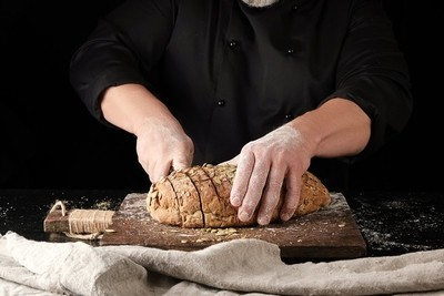 baker in black uniform cuts a knife into slices of rye bread with pumpkin seeds on a brown wooden board