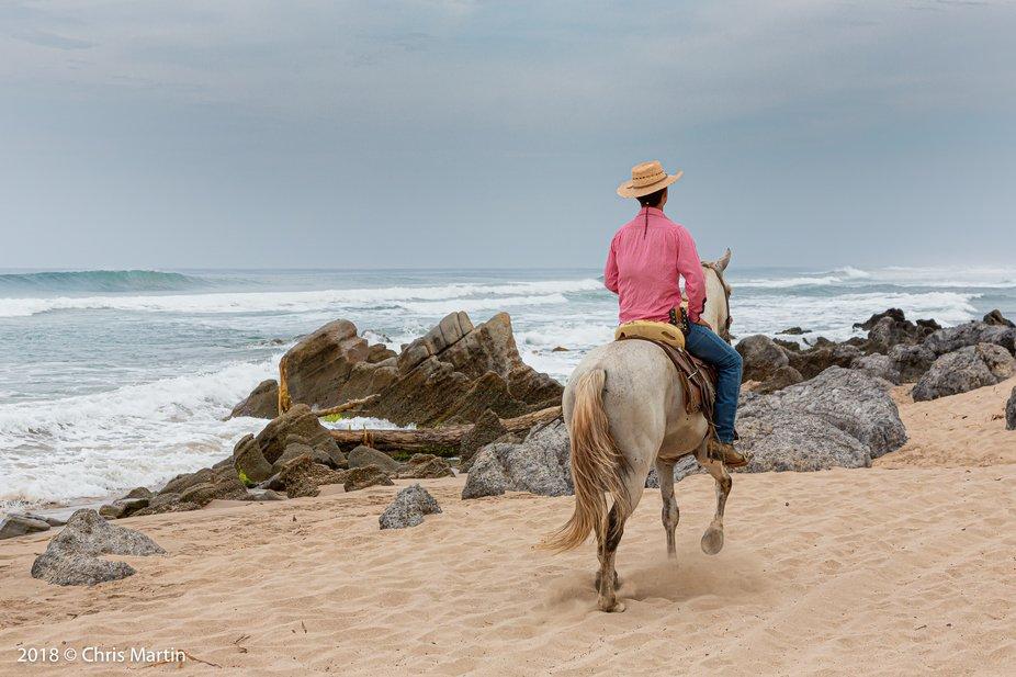 A cowboy rides his horse down the Troncones beach.