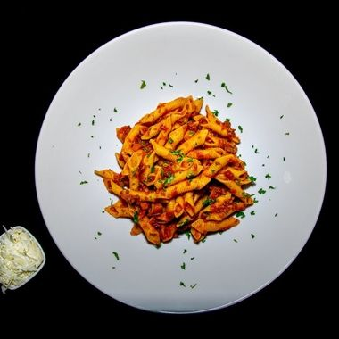 a tasty spicy tomato Bolognese served with penne pasta and a side of parmesan cheeses