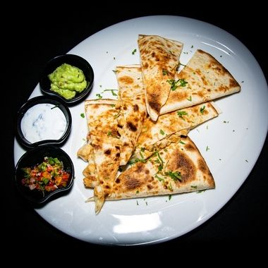 a traditional chicken quesadilla filled with cheese and accompanied with a trio of dips
