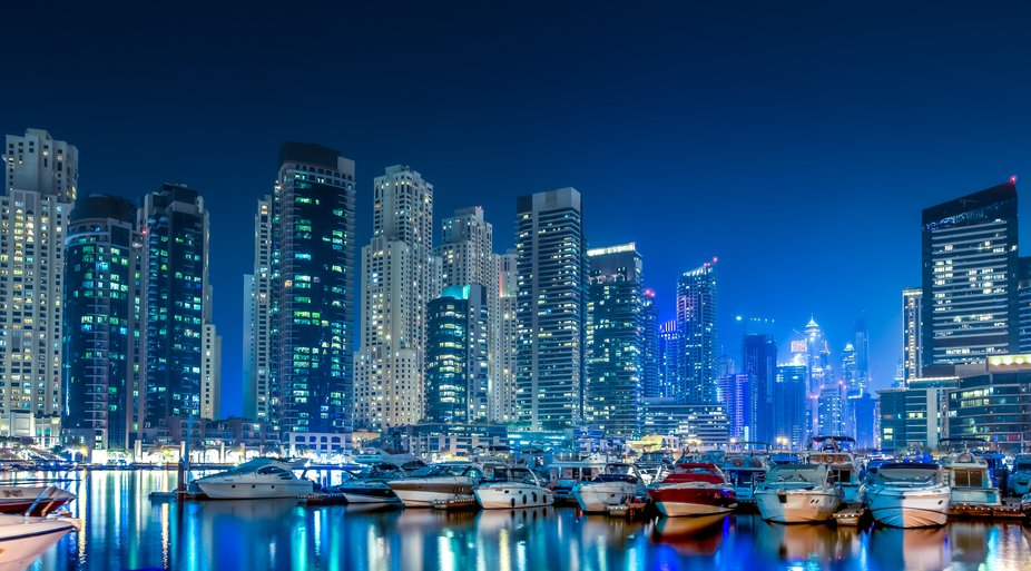 Nightshoot in Dubai Marina. Imposant the boats between all the skyscrapers
