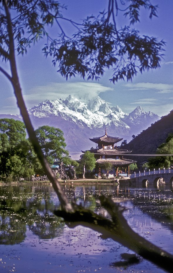 This peaceful lake is found in Lijiang City, Yunnan Province, China. In the distance lies Yulong Shan (Jade Dragon) Mountain, whose highest peak reaches 5,600 m (18,360 ft).