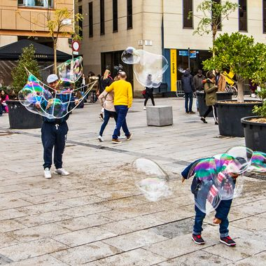 In the plaza, facing the Barcelona Cathedral, this little boy took advantage of a large bubble floating close to the ground.