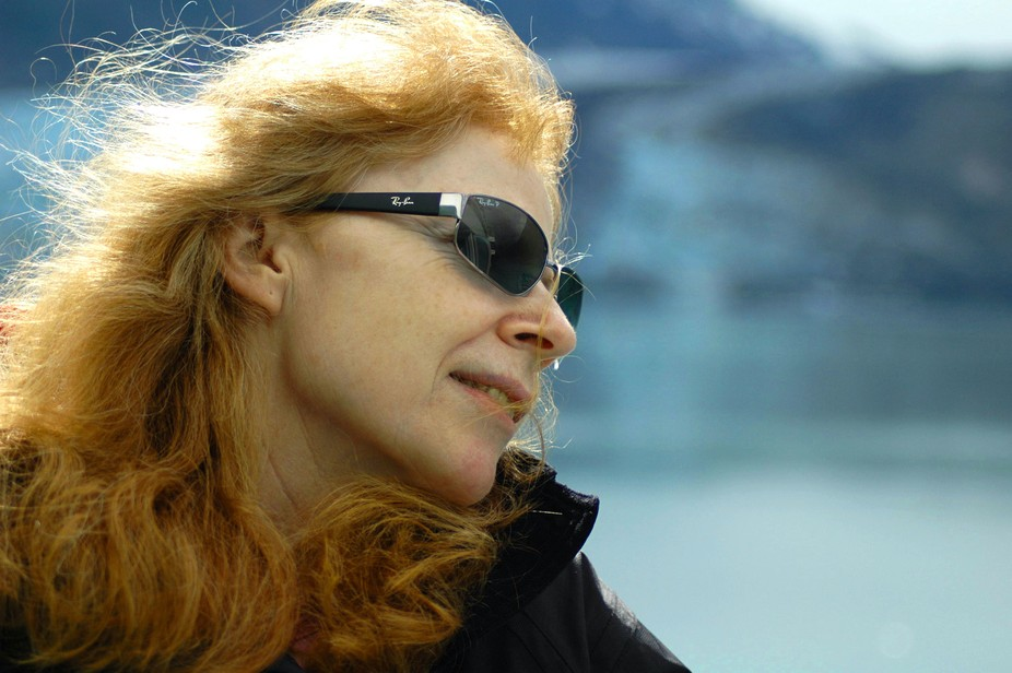 Portrait of my partner taken on an Alaskan cruise ship, with iceberg as the backdrop. Her red hai...