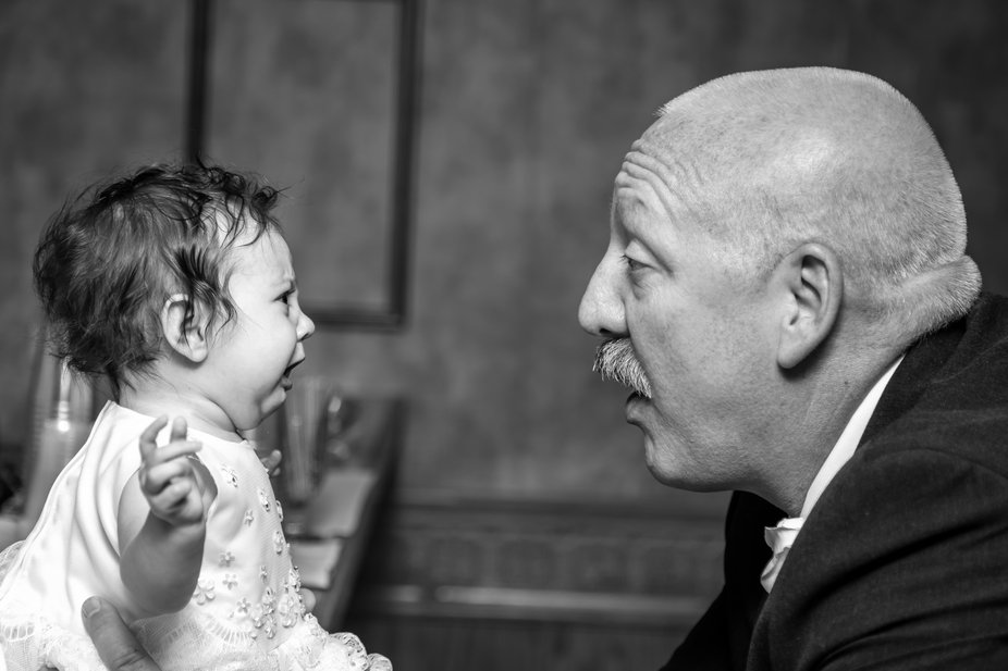 A grandfather is cooing his upset granddaughter at a family gathering and wedding.