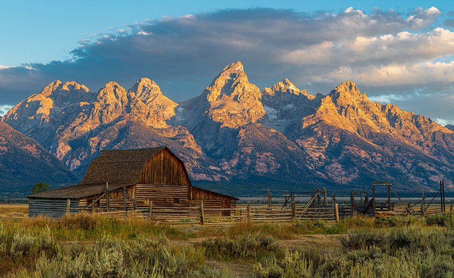 The sun's first rays light up the Grand Teton with the north barn of Mormon Row Historic...