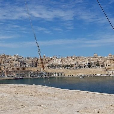 A view of Valletta from Citta Vittoriosa (Birgu) across the Great Harbour.  The ropes on the bastions are holding the recently restored (August  2019) ship mast of HMS St. Angelo (the only shipmast standing in Malta today).  Photo taken during rare occasion when upper level of fort St. Angelo is open to the public.  This area is usually restricted, being still owned by the Knights of the Order of St. John.