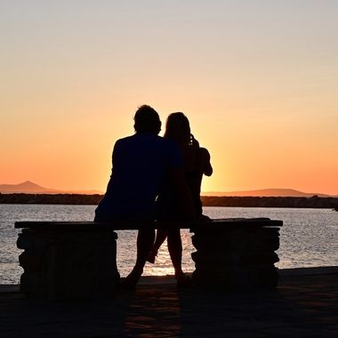 Couple of lovers, silhouette from behind, Golden sunset Naxos Greece