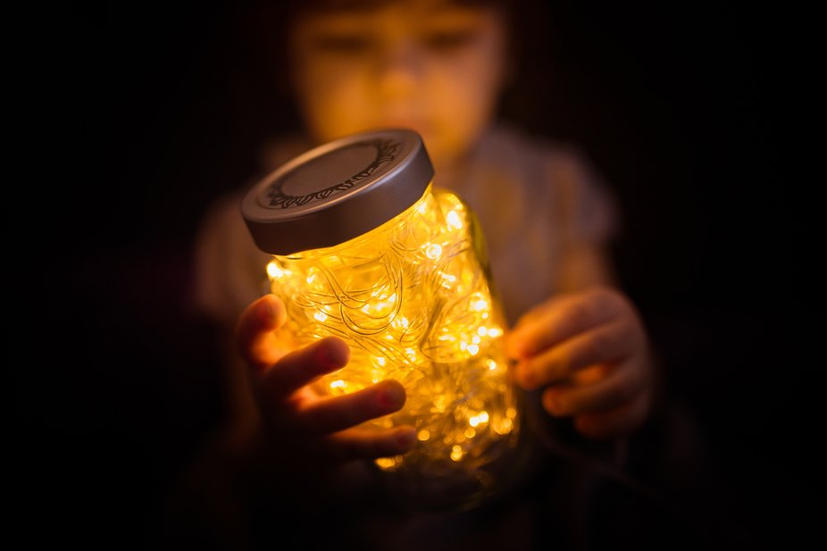 Olivia playing with a jar and lights.