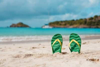 Green flip flops in the white sandy beach near sea waves, nobody. Summer vacation concept with blue water. Relax, vacation on tropical island