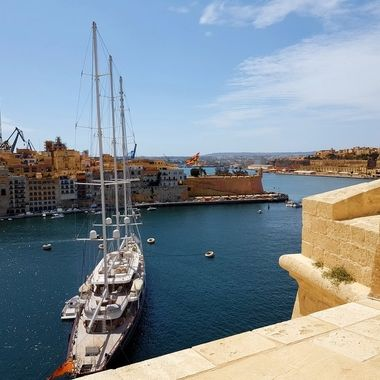 """A superyacht is anchored below HMS Fort St. Angelo in Malta's Grand Harbour.  Just opposite is the """"Gardjola"""" a stone watchtower jutting out from the bastion at the end of the peninsula - a historic symbol of the sentinels that once guarded the villages further inland from marauding vessels."""
