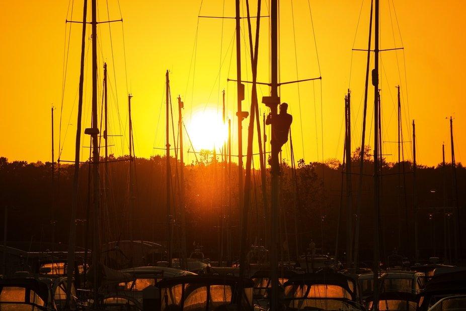 Man fixes his rigging at dusk.