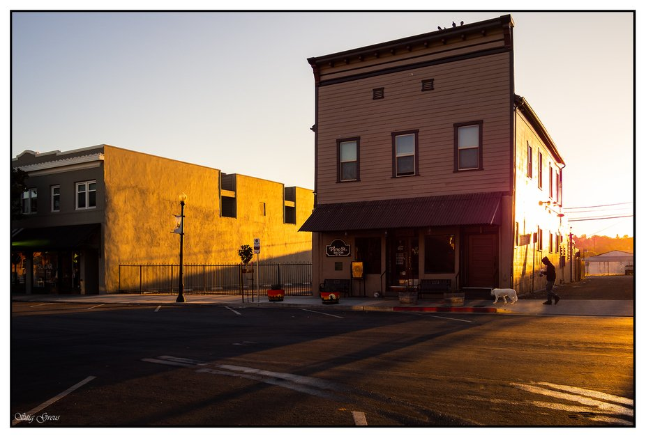 A man walking his dog outside a saloon early in the morning at sunrise.