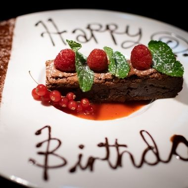 a amazing chocolate brownie decorated with raspberry's and mint leaves and happy birthday written in chocolate