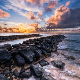 The beginning of another day on the island. The Fisherman still looking for crabs in the breakwater, the sun rising behind colorful clouds at the...