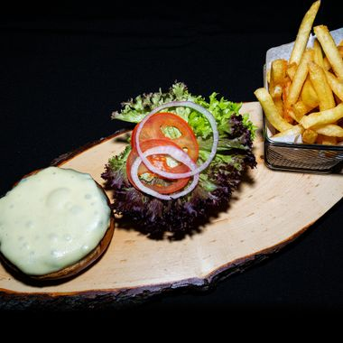 a cheese burger placed on a wooden plate and left open for sauce to be added with the salad on the side alongside a portion of chips