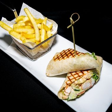 a tasty prawn and avocado served in a tortilla wrap with seafood sauce and accompanied with a side of French fries