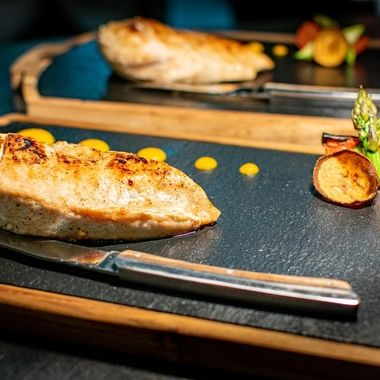 a selection of grilled chicken breast served with their cutting knives and garnish ready to serve to customers