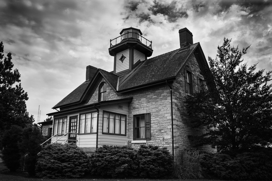 A dramatic black and white photograph of the fully restored Cedar Point Lighthouse on the grounds...