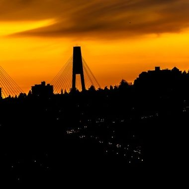 This is a silhouetted view of traffic coming  off of the Puttello Bridge with a pretty orange sky