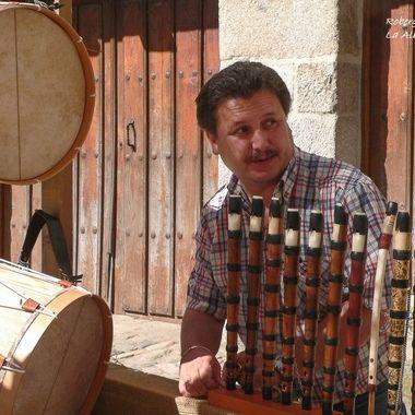 Fabricante de gaitas(Instrumento musical de viento), y tamboril (Instrumento musical de percusion). en un puesto de venta en una Feria tradicional rural.