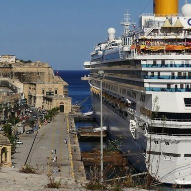 Cruise ship berths at Malta Grand Harbour beneath Valletta city walls.